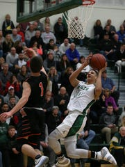 Oshkosh North's Quincy Anderson hangs in the air and gets off a shot against Marshfield's Ethan Posteluk on Friday.