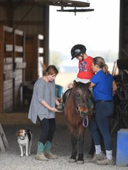 With Walter the farm dog watching, Trish Bartlett, left, and stable owner Stacy Denton help Wesley Clements get saddled up on Daisy the pony before going for a ride at Healing Reins Therapeutic Riding located at Blue Moon Stables in Corydon, Ky., on Friday, Nov. 11, 2016.