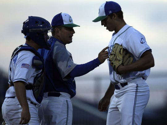 Eagles head coach Dave Tollett, center, talks to relief pitcher Jacob Barnes during the inning as FGCU hosted Miami in baseball at Hammond Stadium in Fort Myers on April 14, 2010. Greg Kahn/Staff