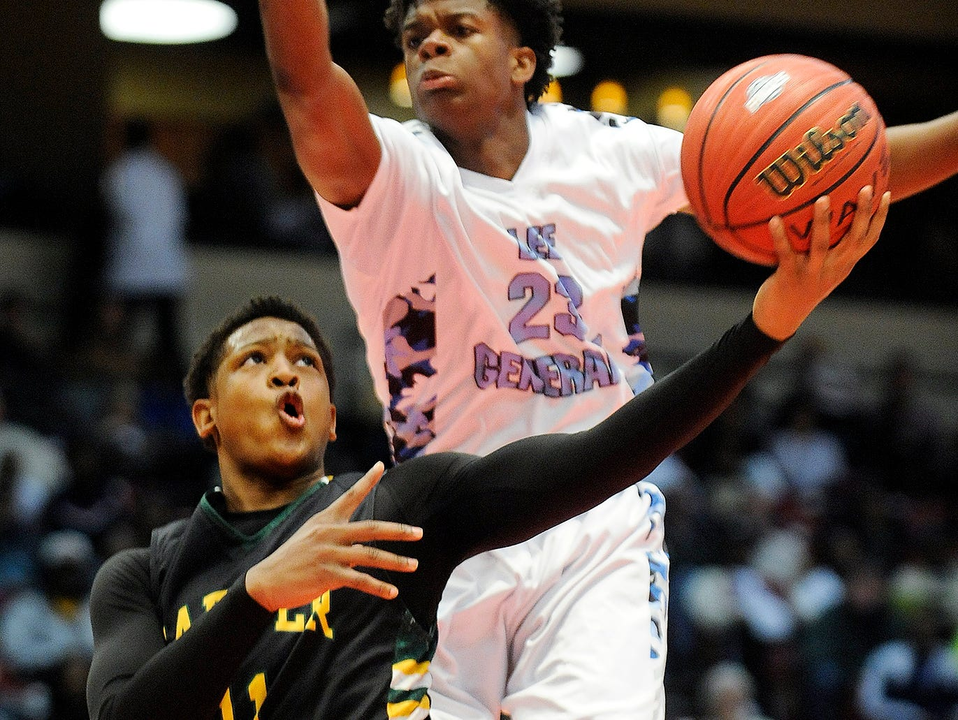 Carver's Darian Adams (11) shoots around Lee-Huntsville's Malik Burnett in the 6A state championship game at the AHSAA State Finals in Legacy Arena at the BJCC in Birmingham, Ala. on Saturday February 28, 2015.