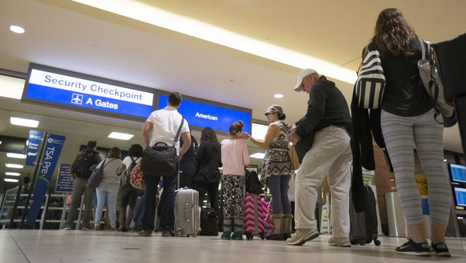 Travelers wait to pass through a security checkpoint at Phoenix Sky Harbor November 24, 2015.