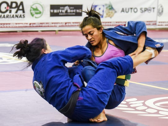 Tassia Pimenta, left, and Emma Xiong compete for the bronze medal in the female black belt category during the 2017 Copa de Marianas Brazilian Jujitsu Tournament at the Father Duenas Memorial School's Pheonix Center in Mangilao on Saturday, Oct. 28, 2017.