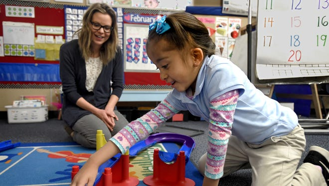 Mackanzie Peterson, of the Desert Research Center, watches Kimberly Jimenez roll a ball in a roller ramp she built at Pine Middle School where Peterson participated in the 2018 Principal for a Day.