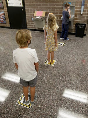 T.C. Knapp Elementary first-grade students from rear, Gabe Griffin, Bailey Witmer and Gavin Pappas keep their distance while getting a drink from the water-filling station.