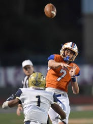 Madison Central quarterback J.D. Hull (7) throws into