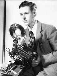 Manhattan Project photographer Ed Westcott poses with the main tools of his trade: a Speed Graphic camera and flash attachment.