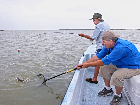 Capt. Kevin Sims scoops another redfish from Mesquite Bay for Bob Gordon.