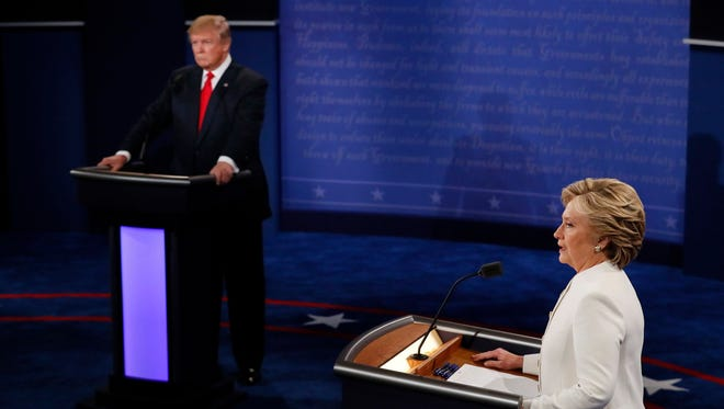 Democratic presidential nominee Hillary Clinton speaks as Republican presidential nominee Donald Trump listens during the third presidential debate at UNLV in Las Vegas, Wednesday, Oct. 19, 2016.