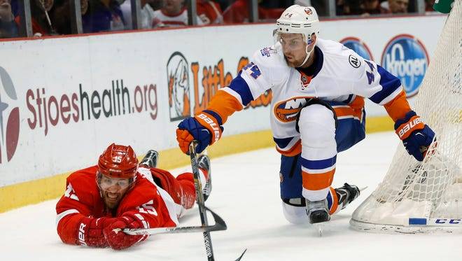 Detroit Red Wings center Riley Sheahan and New York Islanders defenseman Calvin de Haan (44) reach for the puck in the second period of an NHL hockey game Saturday, Feb. 6, 2016 in Detroit.
