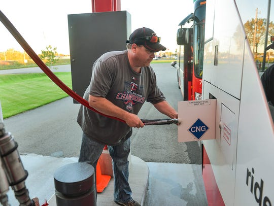 Fueler James Walz fills a MetroBus with compressed
