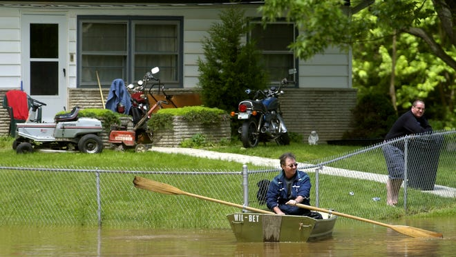 5-14-2002        Tim Myers hops in the rowboat belonging to homeowner Kathy Fishburn during the flooding due to the rising White River in Ravenswood Tuesday morning. The rising flood waters took Finch Street and many others around it. With water still rising the river is to crest tonight leaving the river at its weekly high. (MATT DETRICH PHOTO) File 70281 w/story.
