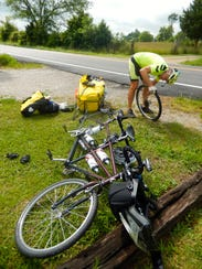 Dana Miller works on fixing a flat tire on his tandem