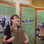 Patrice Melnick demonstrates how to use a scrubboard at the history of zydeco music exhibit located in the Le Vieux Village Tourist and Information Center.