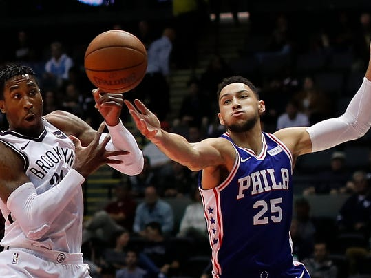 Brooklyn Nets forward Rondae Hollis-Jefferson, left, and Philadelphia 76ers guard Ben Simmons (25) reach for a rebound during the first quarter of a preseason NBA basketball game, Wednesday, Oct. 11, 2017, in Uniondale, N.Y. (AP Photo/Julie Jacobson)