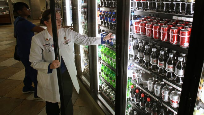 Dr. Taryn Bragg, a pediatric neurosurgeon, grabs a beverage from the cooler at Four Lakes Cafe at UW Hospital in Madison in August. UW Health says it will remove sugary drinks, as well as the deep fryers at UW Hospital, from its facilities by the end of the year.