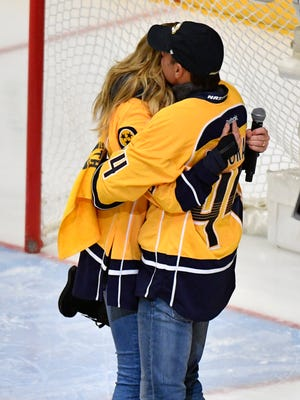 Towel waver Tim McGraw hugs his wife Faith Hill after she sang the National Anthem before game 6 of the Stanley Cup Final at Bridgestone Arena Sunday, June 11, 2017, in Nashville, Tenn.