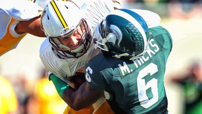 Wyoming Cowboys quarterback Colby Kirkegaard is sacked by Michigan State Spartans linebacker Mylan Hicks during the 2nd half of a game at Spartan Stadium. MSU won 56-14.