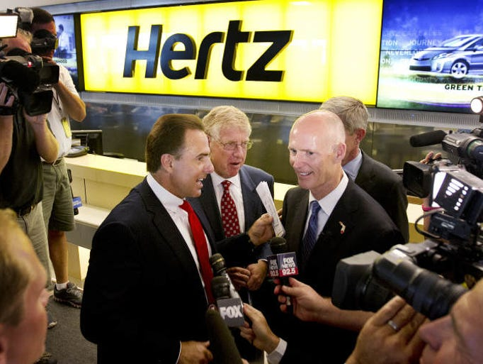 Hertz CEO Mark Frissora, left, and Florida Governor Rick Scott are surrounded by media after a press conference at Southwest Florida International Airport announcing the company's move to Southwest Florida.   Hertz is moving its world headquarters to Estero.  At center is Daniel Dosaretz, CEO of 21st Oncology.