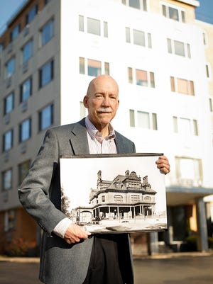 Donald Hall holds a photo of the Cunningham mansion, which stood where this condominium building now stands (at 1000 East Ave.).