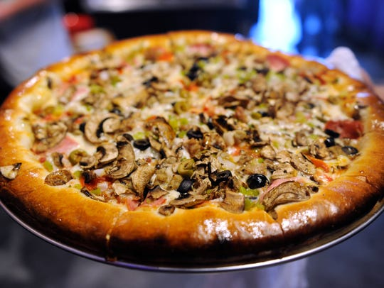A supreme pizza is brought out to the buffet during
