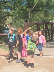"Children from Jose Barrios Elementary School cross the bridge each day at the Silva Creek Botanical Gardens.  Children who use the bridge to meet their family after school are fondly called ""bridgers,"" and school staff walks them to the bridge each day.  Students pictured (left to right) Ila Rose Duffy, Dara Werber-Raiter, Evan Bighley and Izabella Torres."