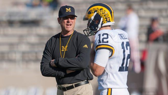 Michigan coach Jim Harbaugh chats with punter Blake O'Neill before Saturday's game at Indiana.