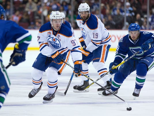 Edmonton Oilers' Connor McDavid (97) skates with the puck while being chased by Vancouver Canucks' Alex Biega (55) during the first period of an NHL hockey game Saturday, April 8, 2017, in Vancouver, British Columbia. (Darryl Dyck/The Canadian Press via AP)