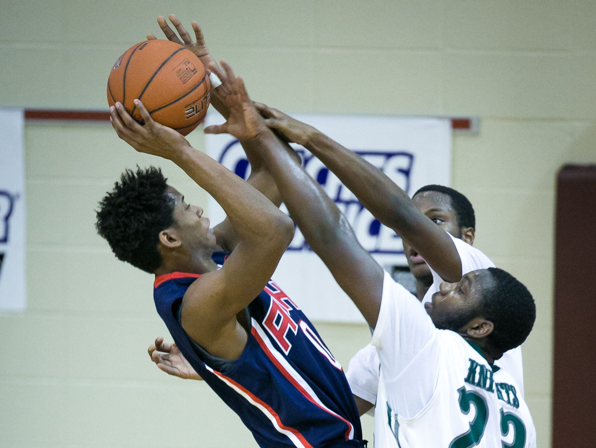 Yvens Monfluery (left) of American History gets blocked by two Mount Pleasant players late in the game.
