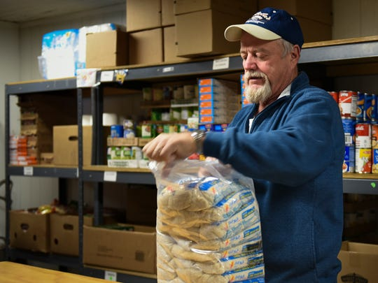 Volunteer Stu Taylor of Olivet organizes food Tuesday,