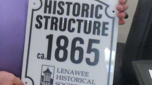 One of the historical markers that will be presented to building owners of the Lenawee County Historical Society's Historic Structures Program is pictured. Intended to be mounted on the building to identify historic buildings and structures, the homes and structures that will be receiving the signs are certified under the Lenawee County Historical Society's Historic Structures Program.