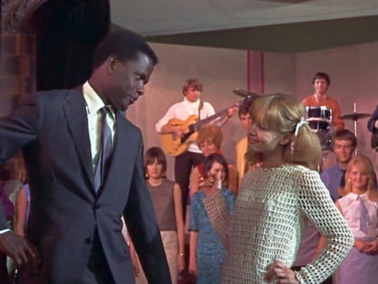 Sidney Poitier and Judy Geeson dancing in a scene in