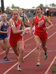 Bellevue's Lauren Turner takes the baton from Liz Ish in the 4x400 relay at the Division II district meet.