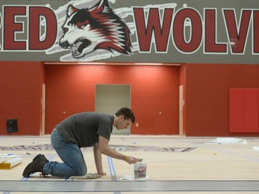 Chris Schlenker paints the gymnasium floor Friday,