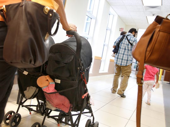 Isabel Martinez, left, pushes an empty stroller from the courtroom while her two granddaughters walk ahead with her son, Bryan Thursday.