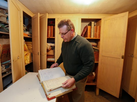 Alan Frohberg, a temple board trustee, looks though old records of the Masonic Temple.