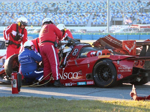Rescue workers remove driver Memo Gidley from his car after he was involved in a crash during the IMSA Series Rolex 24 hour sports car race at Daytona International Speedway in Daytona Beach, Fla., Saturday, Jan. 25, 2014. (AP Photo/Dow Graham)