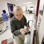 """With his cane and guitar in hand, Donald """"Donnie"""" Orton takes the elevator from the fifth to the third floor at St. Joseph's Hospital in Elmira to perform for residents."""