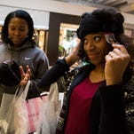Carrington Malone tries a hat on at SoHo Fashion while shopping with friend, Riyan Mitchell, during Black Friday, Nov. 27, 2015, at Mall St. Matthews in Louisville, Ky.