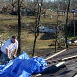 David McCullar with DNS Siding helps lay down tarp on a roof of a home on Falcon Road in Selmer on Thursday morning. A tornado came through the area Wednesday evening, knocking down trees, power lines, and destroying some homes in the area. No deaths or injuries were reported.