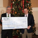 Gettysburg Hotel General Manager Chuck Moran, left,  presents James Dunlop, founder and president of Ruth's Harvest, with a donation of $500 on behalf of the associates of the hotel.