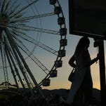 A woman is silhouetted as the sun sinks for the final time for the 2016 Coachella Valley Music and Arts Festival in Indio, Calif., on Sunday, April 24, 2016.
