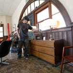 Deb Toman, co-owner of AtomicKatz in Oshkosh, sits on a mid-century modern couch.  Her store sells furniture and other items from the 1950s through the 1970s.