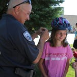 Indianola Police Capt. Brian Sher helps 11-year-old Shannon Alexander with the fit of her bicycle helmet during the Indianola Parks and Recreation Bike Rodeo on the Indianola Square on June 18.