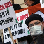 Activists rally in January 2013 at New York's City Hall for immediate action on paid sick days legislation. New York City and two New Jersey cities, Jersey City and Newark, are the latest to require employers to give workers paid time off when they're ill or to care for sick relatives.