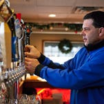 Pittsford Pub's new owner, Scott Thyroff, changes a beer tap at the bar on Dec. 18.