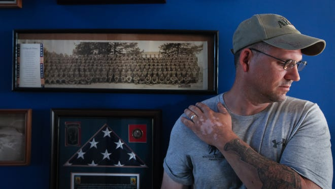 Kevin Conley stands against the wall where old photos of family members in the military hang at their home in Middletown, Delaware.