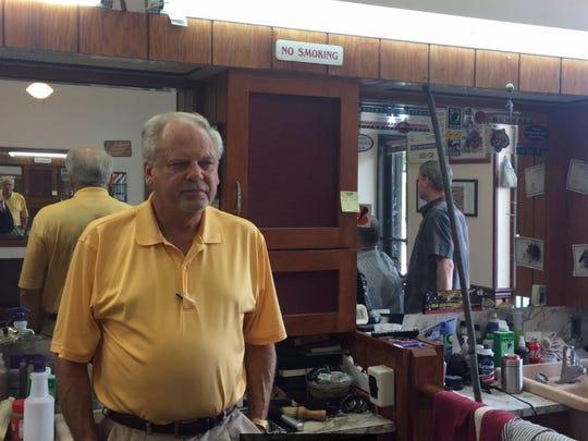 Donald Vaughn stands inside of his Village Barber Shop