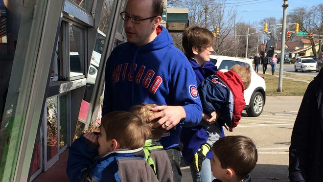 Phil James and his sons stand in line at Snookies Malt Shop in Beaverdale. They were the first customers this morning as the shop opened up for the season. (Lauren Horsch/The Register)