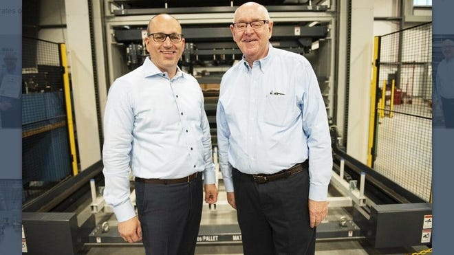 """In this photo taken in September 2019, Salem Metal President and CEO Jason Vining, of Middleton, and his father James, who is the executive vice president of the company, stand in front of their newly acquired, automated, material tower system. This system enables """"lights-out"""" laser cutting during week nights and weekends for high-volume production."""