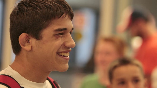 Yianni Diakomihalis, 16, is all smiles as he visits with friends at the Greater Rochester International Airport Monday, Aug. 31, 2015. Diakomihalis, going into his junior year at Hilton, won the gold at The United World Wrestling Cadet Freestyle World Championships in Bosnia in the 127.6-pound weight class over the weekend.